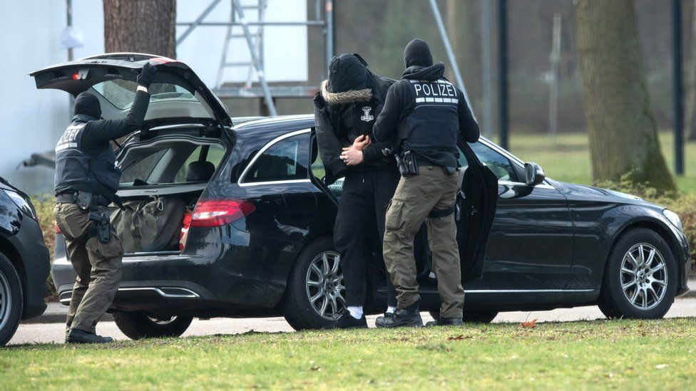 A person is brought to the Federal Supreme in Karlsruhe, Germany, by police officers, 15 February 2020