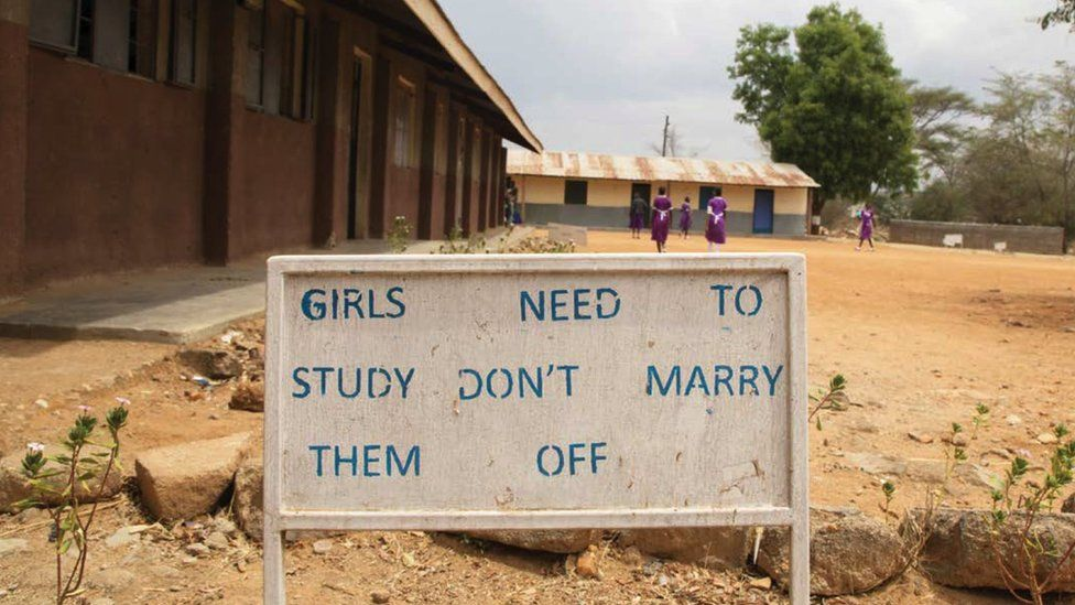 "A school playground in Africa - a billboard reads ""Girls need to study, don't marry them off"""