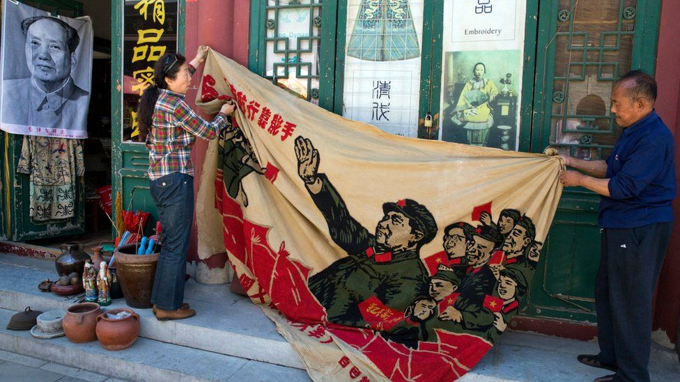 """Vendors at a curio market in Beijing unfurl a banner from 1969 depicting former Chinese leader Mao Zedong, surrounded by Red Guards and the slogan """"navigating the seas depends on the helmsman"""" on 16 May 2016"""