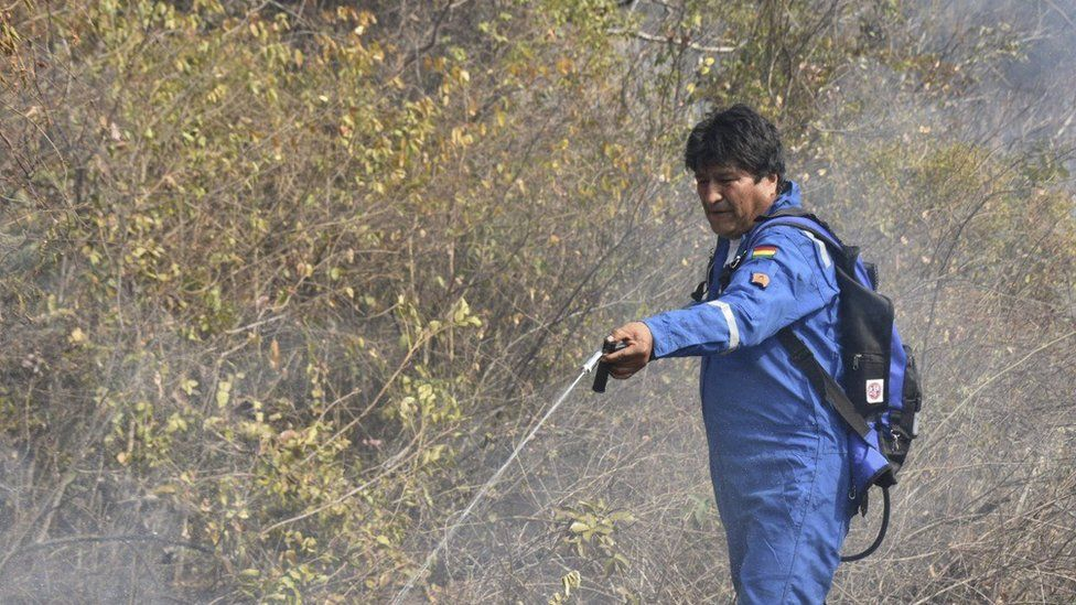 Bolivian President Evo Morales spraying water at a fire in the community of Santa Rosa, near Robore in eastern Bolivia, on August 28, 2019