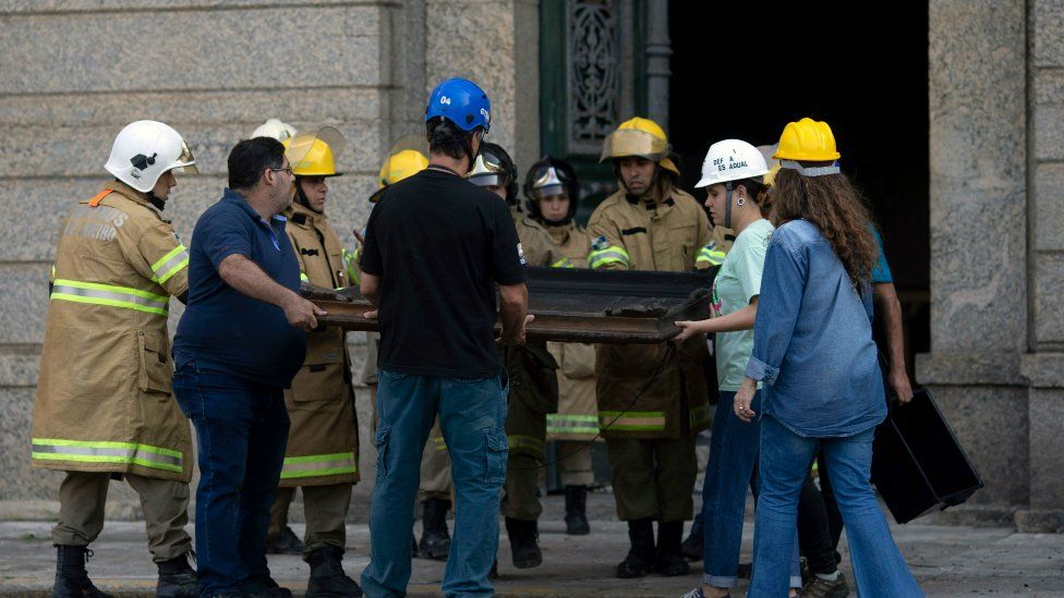 Museum staff and firefighters take a painting from the debris of Rio de Janeiro's National Museum on September 3, 2018