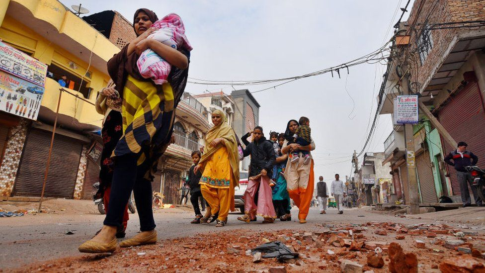 People leave their houses following communal violence over the Citizenship Amendment Act (CAA), in Shiv Vihar area on February 27, 2020 in New Delhi, India