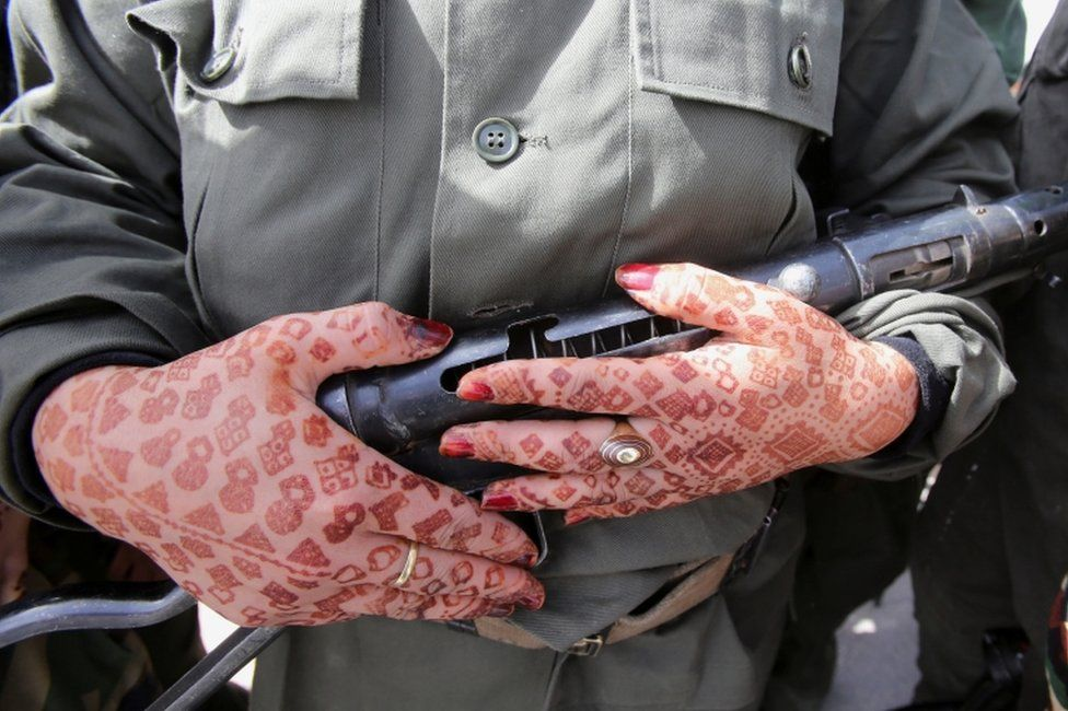A Sahrawi woman soldier holds a gun. She has henna-dyed patterns on her hands.
