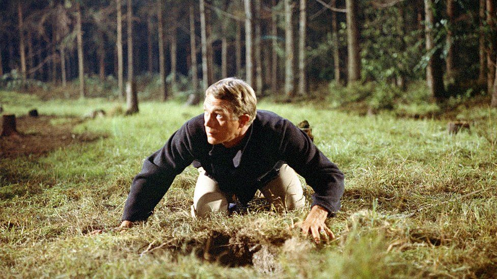 Steve McQueen emerges from a tunnel in The Great Escape