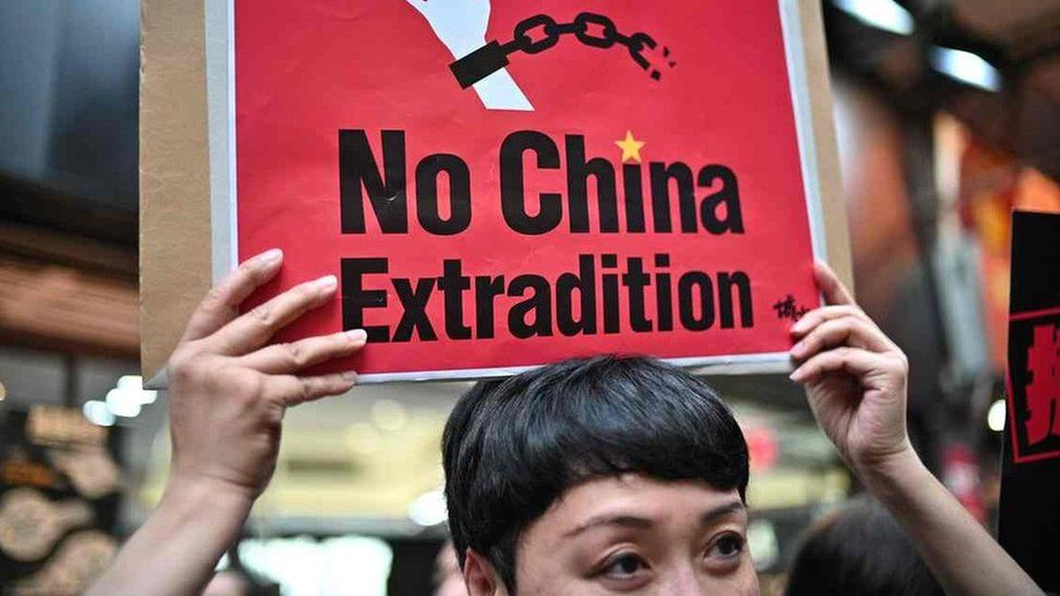 A protester holding a sign reading no China extradition