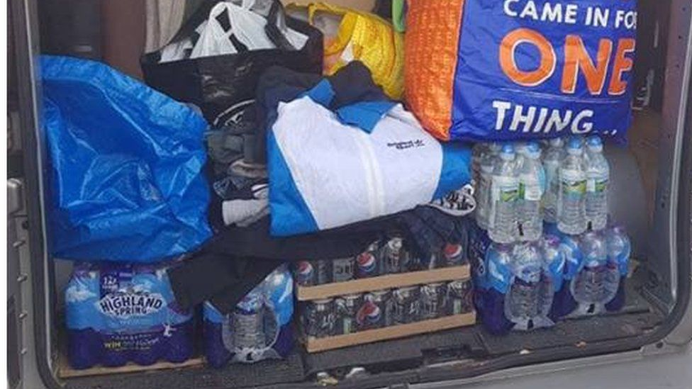 The back of a van loaded with bottled water and other items