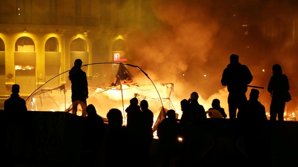 Protesters stand near burning tents during anti government protests in Beirut