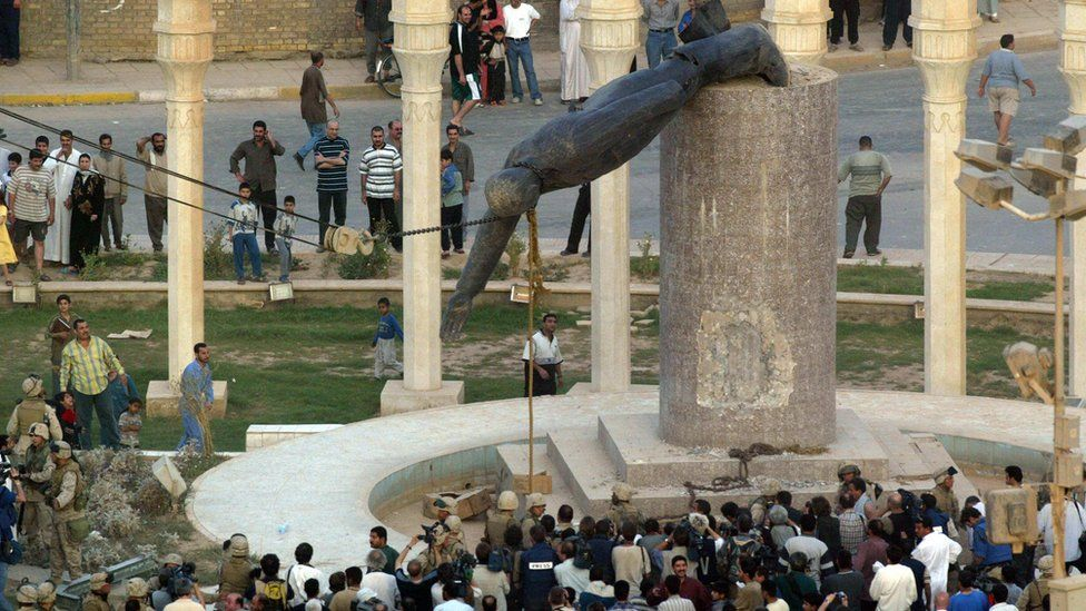 "Iraqis watch a statue of Iraqi President Saddam Hussein falling in Baghdad""s al-Fardous (paradise) square 09 April 2003."