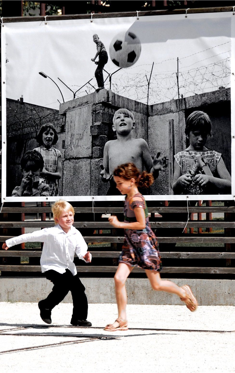 Children run in a playground in Berlin that has an old picture of children playing by the wall.