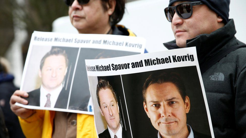People hold signs calling for China to release detainees Michael Spavor and Michael Kovrig during an extradition hearing for Meng Wanzhou
