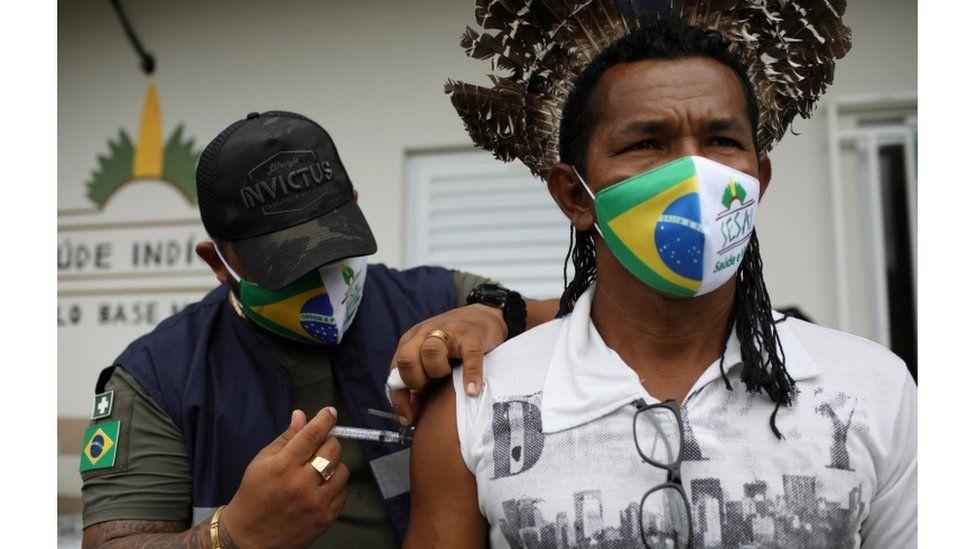 Медицинский агент Специального санитарного округа для коренных народов Манауса вводит вакцину против коронавируса уроженцу деревни Макира, принадлежащему к этнической группе Мура, на берегу реки Урубу в Итакоатиара, Амазонас, 13 февраля 2021 г.