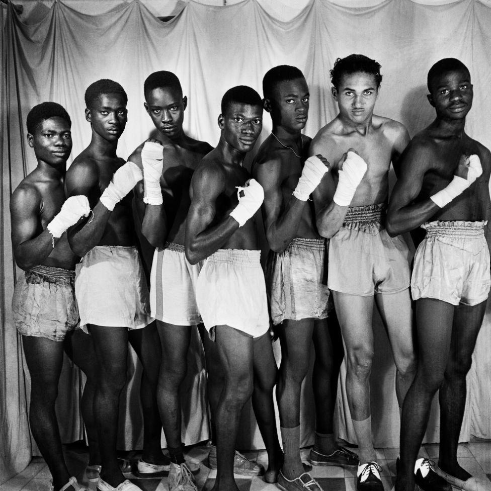 Men dressed in boxing shorts with bandaged hands pose in a line for the camera.