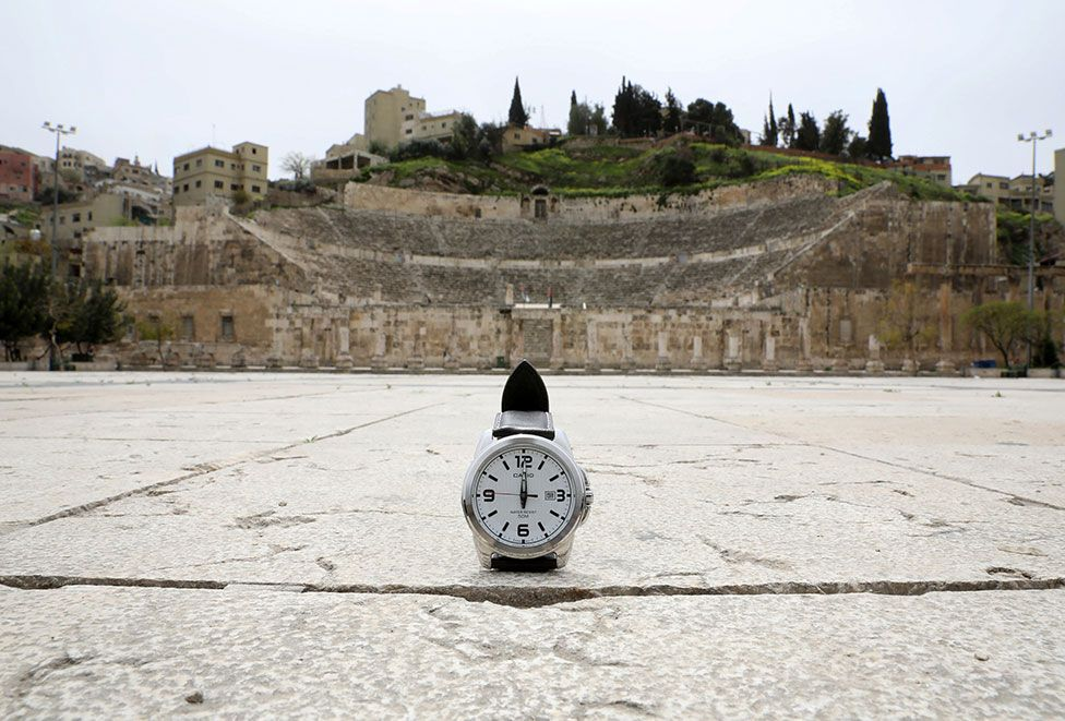 A watch showing the time at noon in front of the Roman theatre in Amman, Jordan