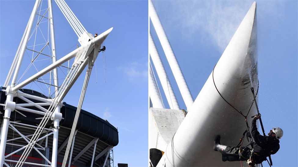 An image of an abseiler cleaning the stadium mast