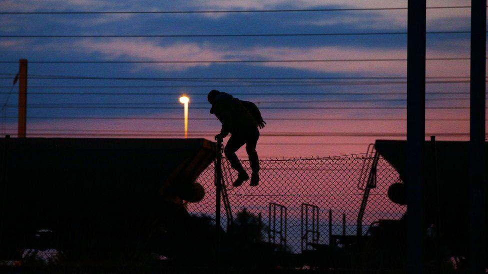 A migrant climbs onto a train in Coquelles, Calais