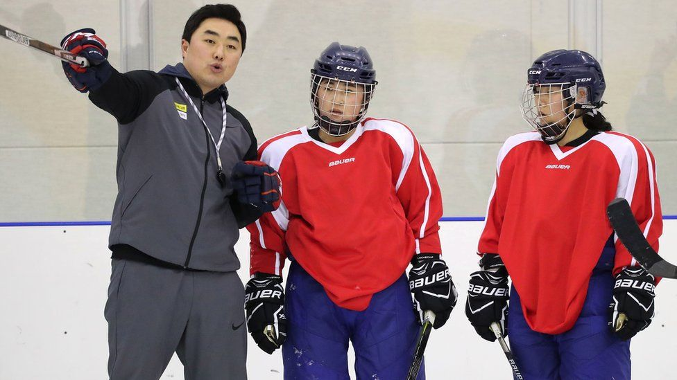 North Korean players talk to their South Korean coach in training for the 2018 Winter Olympics.