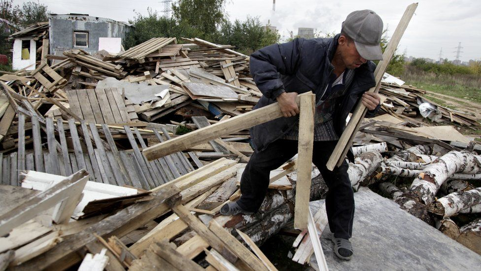 A Tajik migrant worker gathers wood in Moscow on September 23, 2009
