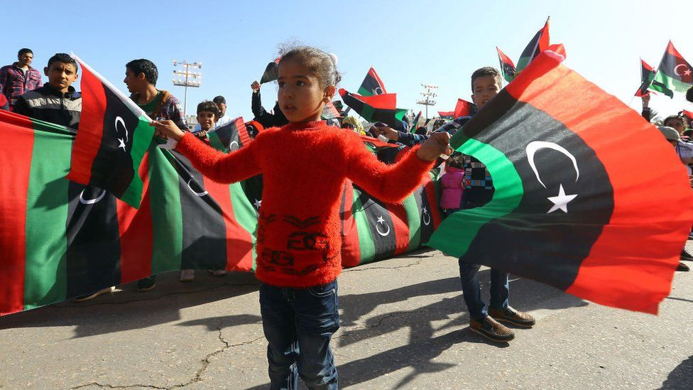 A Libyan girl waves her country's national flag as she takes part in a celebration marking the sixth anniversary of the Libyan revolution, which toppled strongman Moamer Kadhafi, at the Martyrs' Square in the capital Tripoli, on February 17, 2017.