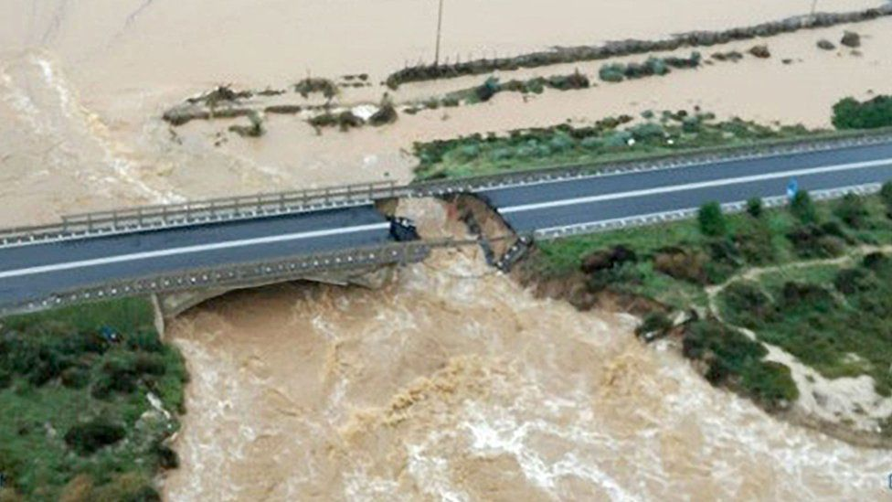 An aerial shot shows a bridge, collapsed in its centre with raging brown water below
