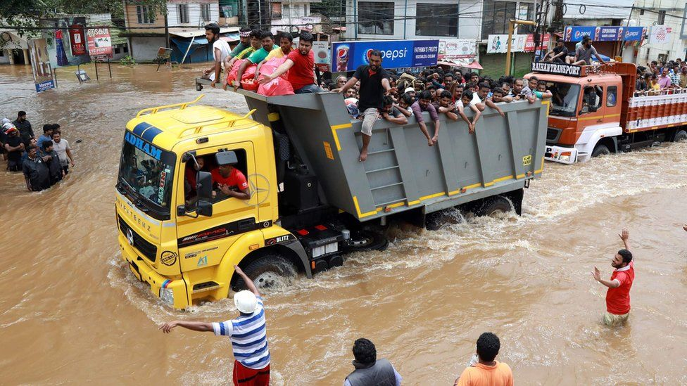 Indian passengers travel in a truck to a safer place as flood waters ravage the National Highway 47 in Ernakulam district of Kochi