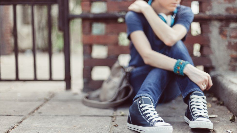 A person sits alone on the street. Their converse are visible in the foreground. They are quite blurry. The picture feels a bit lonely.