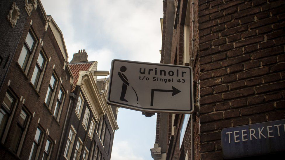 A sign pointing to a men's urinal in Amsterdam