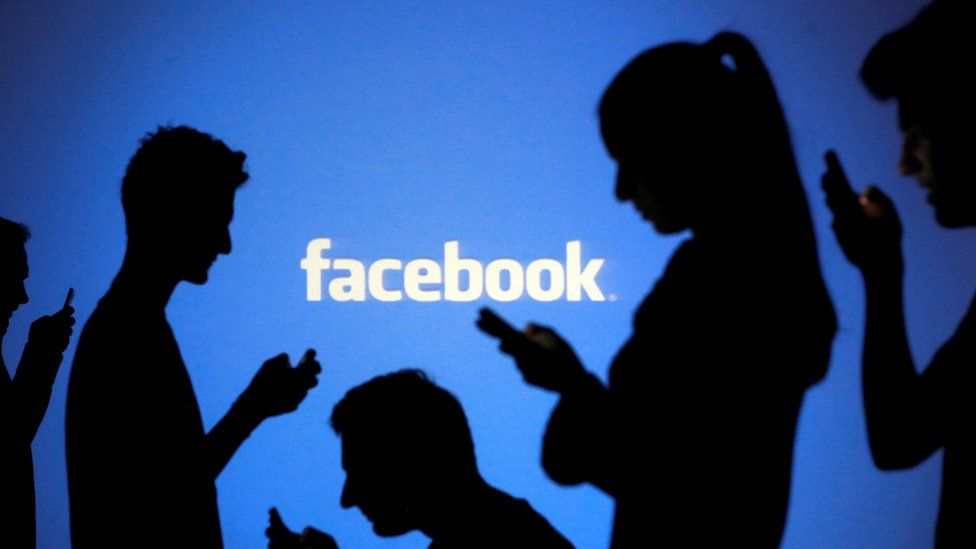 Silhouetted figures stand in front of the Facebook logo