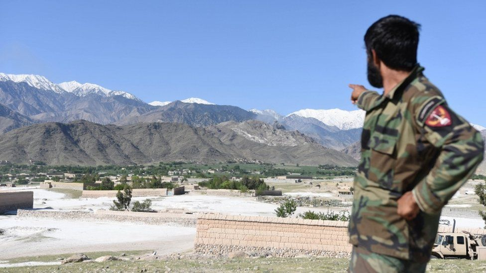 An Afghan soldier points to the area where the US dropped the bomb