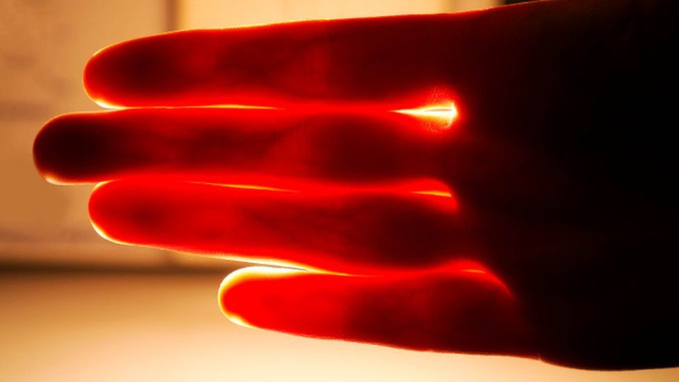 Red light shining through a person' hand