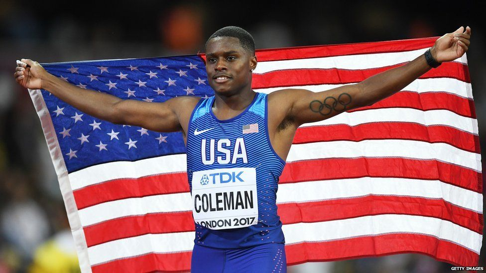 This is a photo of athlete Christian Coleman holding up the American flag.