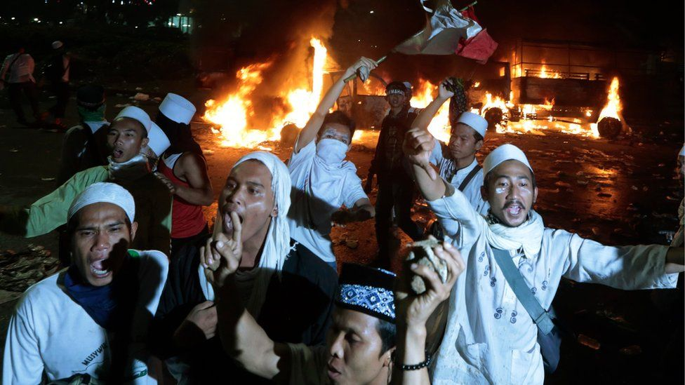 Muslim protesters chant slogans near burning police trucks during a clash with the police outside the presidential palace in Jakarta, Indonesia, Friday, Nov. 4, 2016.