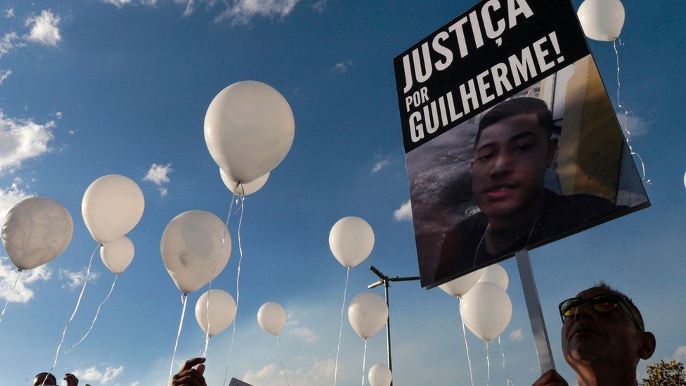 Protesters hold a 'Justice for Guilherme' sign after the 15-year-old was killed in Sao Paulo in June