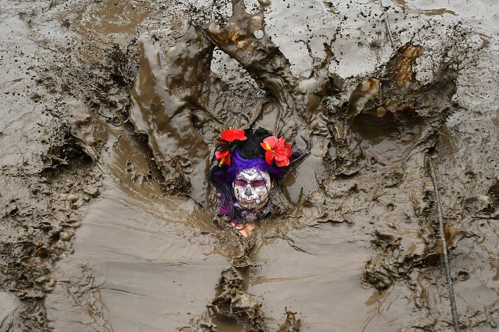 A competitor plunges into the mud during the Tough Guy Challenge.