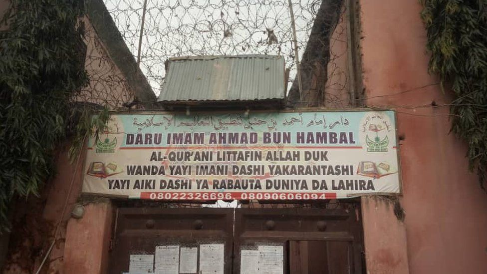 "A sign in the Hausa language outside the school reads: ""Ahmad bin Hambal Centre for Islamic teachings. The Koran is the book of Allah, whoever believes in it, reads it and adopt sit will have salvation in this life and in the hereafter."""