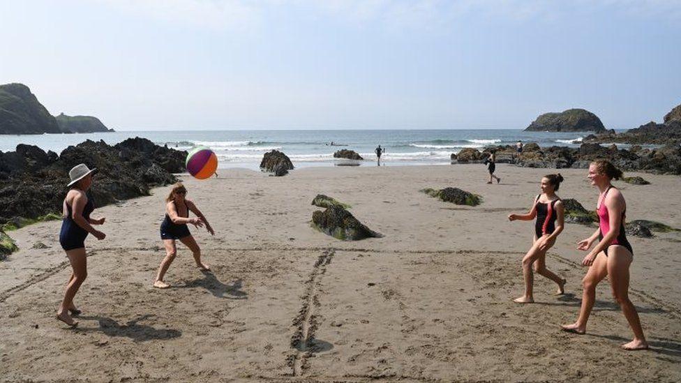 Beachgoers play volleyball in Traeth Llyfn beach in Pembrokeshire