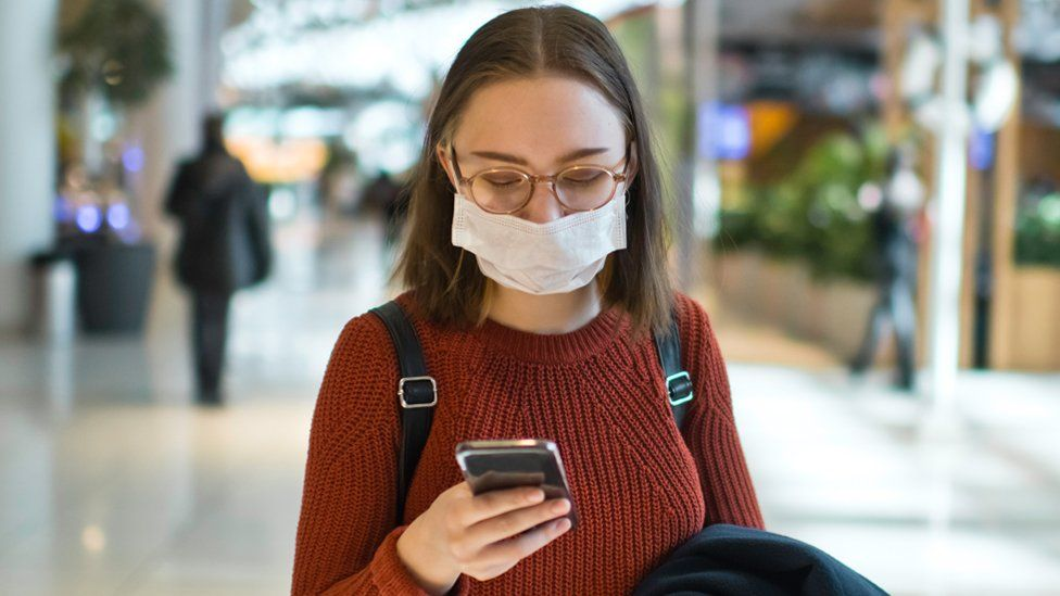 Stock image of a young woman wearing a face mask and holding a smartphone
