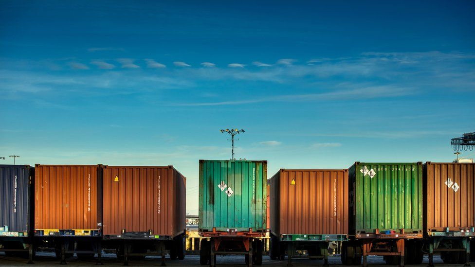 line of trucks carrying shipping containers