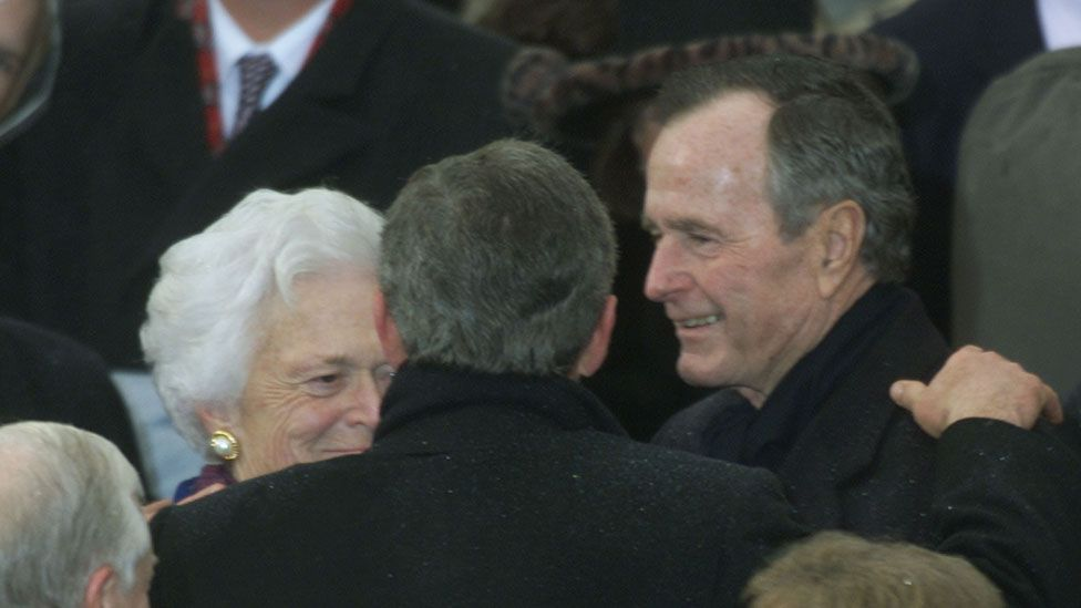 George W Bush embraces his parents following his inauguration