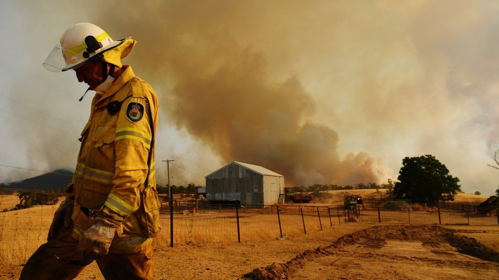 A firefighter in the foreground of the photo with a plume of smoke rising above a barn in the background