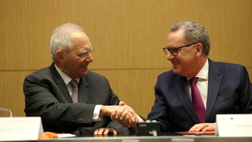 """President of the French National Assembly Richard Ferrand (R) and Germany""""s Bundestag president Wolfgang Schauble shake hands after signing during the launching of the French-German Parliamentary Assembly on March 25, 2019 at the French National Assembly in Paris."""