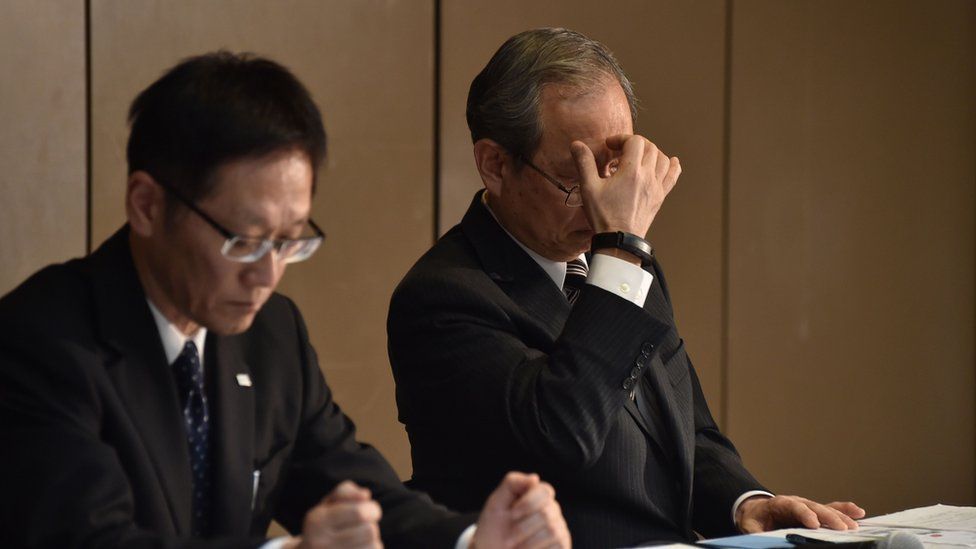 Toshiba Corp. President Satoshi Tsunakawa (R) reacts as he listens to questions during a press conference at the company's headquarters in Tokyo on December 27, 2016