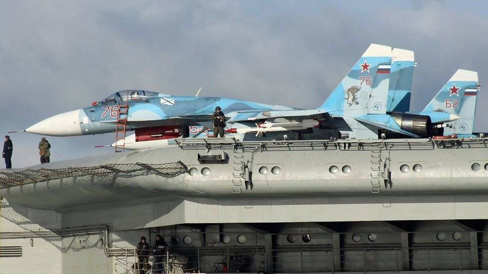 Armed military personnel alongside aircraft on the flight deck of Russian aircraft carrier Admiral Kuznetsov in the English Channel on 21 October