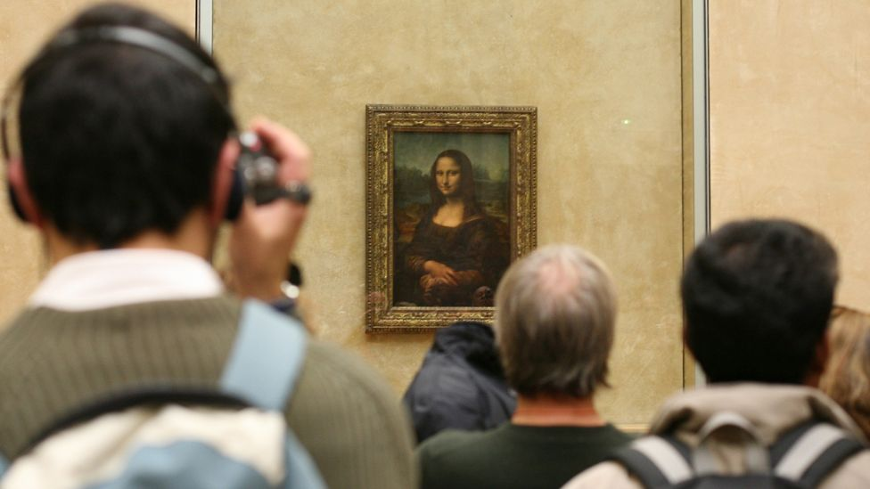 Visitors stand at the Mona Lisa in The Louvre in Paris