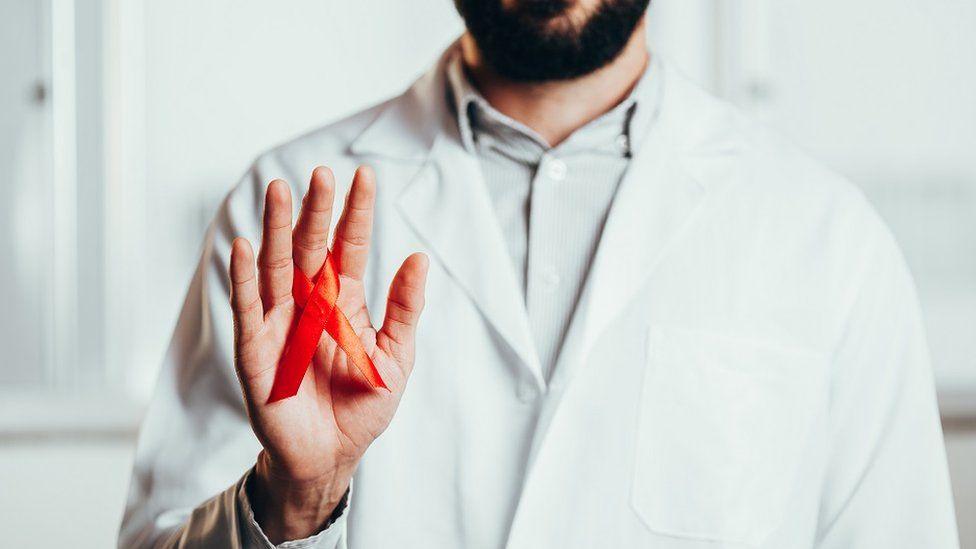 Imagen de un médico vestido de blanco, sosteniendo una cinta roja de concienciación de VIH