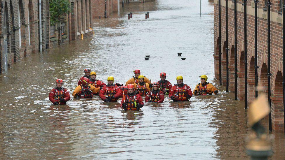 Members of the Mountain Rescue teams wade through floodwater in Skeldergate, York, on 28 December 2015