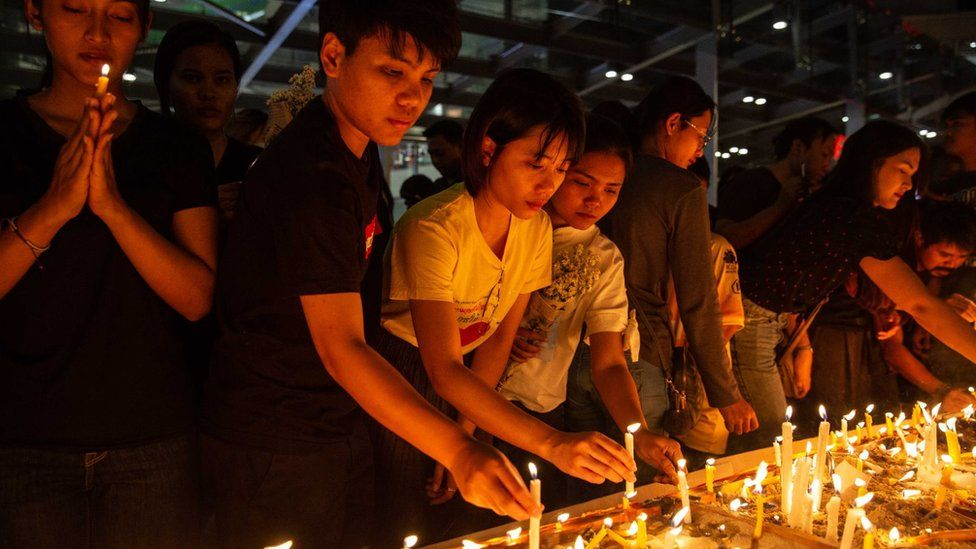 Thai mourners lighting candles