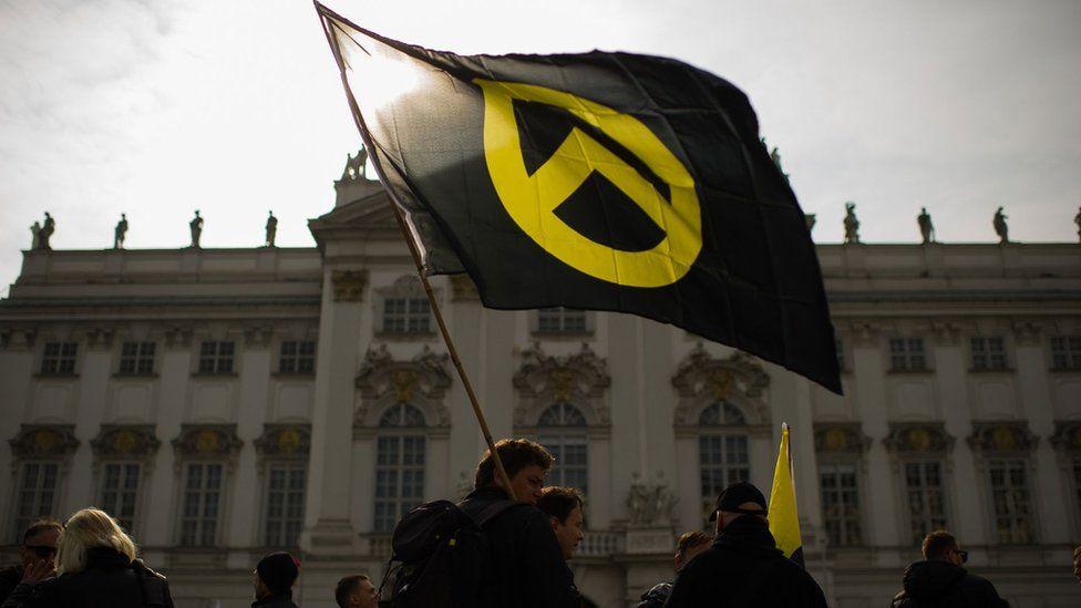 """2019年4月,奥地利""""身份认同的一代""""运动成员在维也纳奥地利司法部大楼前示威。旗帜上是这个组织的图标。"""
