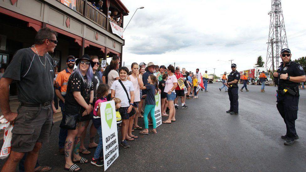 "Demonstrators hold placards saying ""start Adani - Queensland coal powering Australia's economy"""