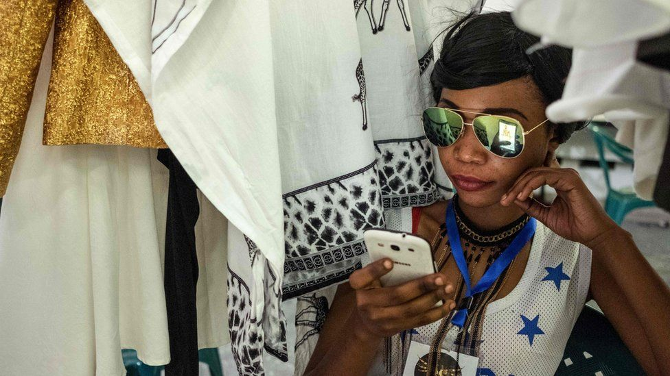 An event organiser looking at a phone at Swahili Fashion Week in Dar es Salaam, Tanzania - Saturday 2 December 2017