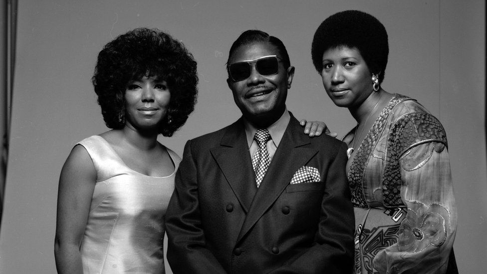 A black and white picture of Aretha Franklin, her father CL, and her sister, fellow singer Carolyn, taken in 1971.